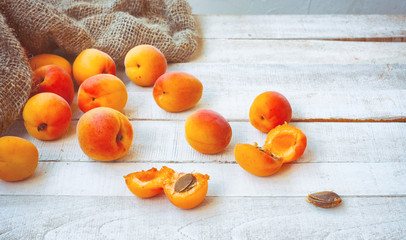 ripe apricots on wooden table, rough burlap sack