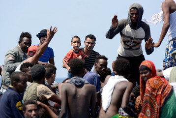 Migrants on a wooden boat react as they wait to be rescued by SOS Mediterranee during a search and rescue (SAR) operation in the Mediterranean Sea