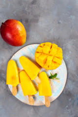 Mango sorbet on round blue tray popsicles seeing from above