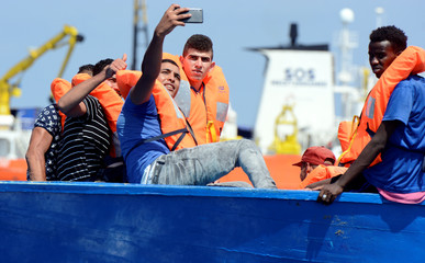 Migrants on a wooden boat take a selfie as they wait to be rescued by SOS Mediterranee during a search and rescue (SAR) operation in the Mediterranean Sea
