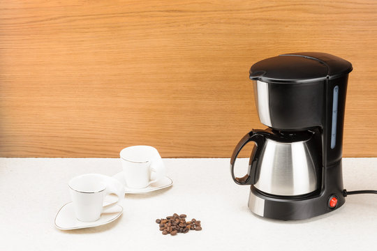 Coffee machine with pot and handful coffee beans on the wood and marble background