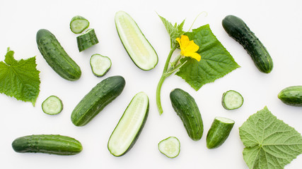 Young cucumbers with cut cucumber and leaf on white