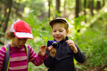 Portrait of children taking photos with a camera in the forest. Scene in the summer, large blur background.