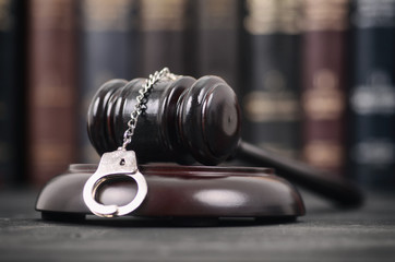 Judge Gavel and Handcuffs on a black wooden background.