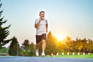 The elderly man running on the road on the sunrise background Wall mural