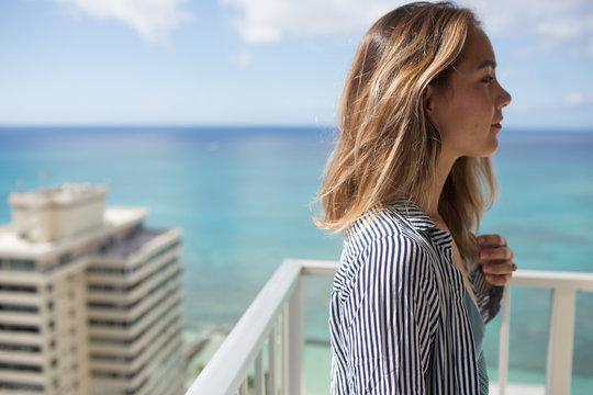 Portrait of woman on balcony, Waikiki, Oahu, Hawaii, USA