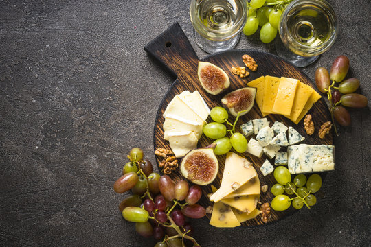 Cheese plate with grapes, figs and nuts.