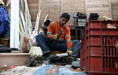 Man separates metals and other materials from a used electronic device at 'A Caminar' recycling plant in Lima