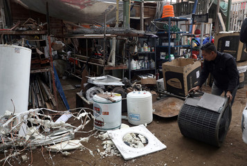 Man separates metals from used electrical appliances at 'A Caminar' recycling plant in Lima