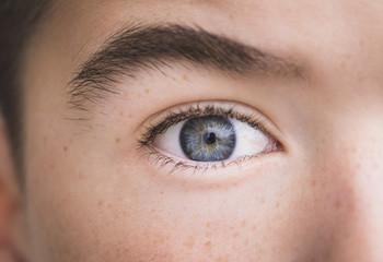 Macro shot portrait of boy with gray eye