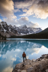 Rear view of man looking at Moraine lake while standing on rock in Banff National Park during sunset
