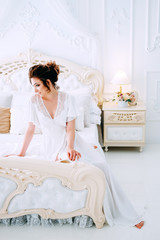 Beautiful young bride in honeymoon suite getting ready
