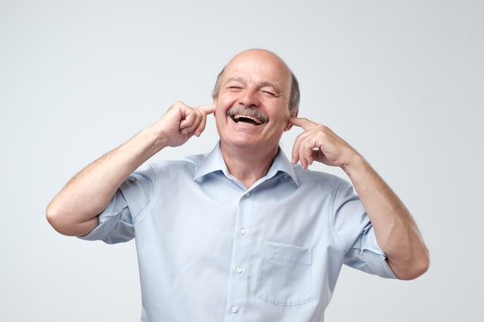 Good-looking happy mature european man smiling with closed eyes, holding index fingers in ears, waiting for surprise