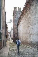 Full length of businessman walking on street amidst buildings in city