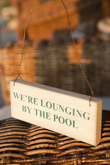 Sign 'We're lounging by the pool' on wicker chairs.