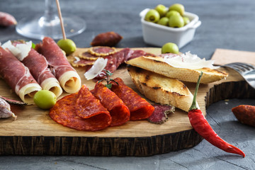 Typical spanish tapas concept. include variety slices jamon, chorizo, salami, bowls with olives, peppers. Copyspace.