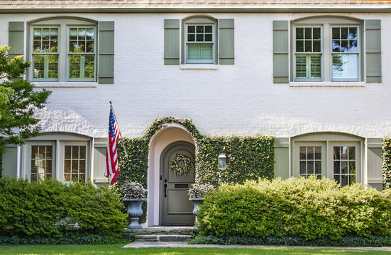 Vine covered entrance to white painted brick house with arched front door and wreath and arched windows with green shutters - landscaped with American flag