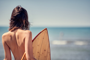 Surfer girl. Sexy woman at the beach -Back view.