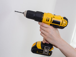 Hand holding yellow drill