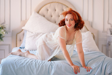 A luxurious pin up lady dressed in a beige vintage lingerie posing in her bedroom alone