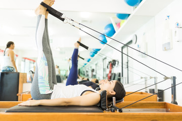 Client Maintaining Her Fitness While Exercising On Reformer Machine