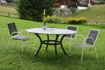 Ein Tisch mit drei Stühlen und Aschenbecher im Garten