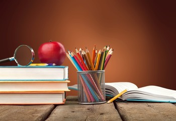 Colorful school supplies on wooden background