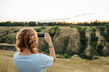 woman tourist taking pictures on the phone nature
