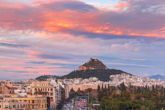 Mount Lycabettus towering above of the roofs of Old Town at gorgeous sunset in Athens, Greece