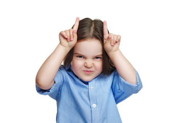 Little girl making teasing gesture with horns