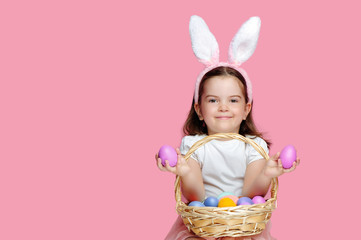 Little girl  holding  pink Easter eggs in her hands  isolated on pink