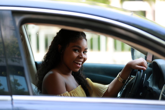 Confident African American woman in car smiling