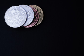 Four shiny crypto coins (left corner) on black surface, free copy text space.