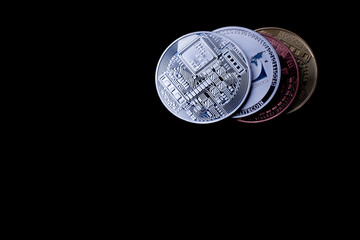 Four shiny crypto coins (right corner) on black surface, free copy text space.