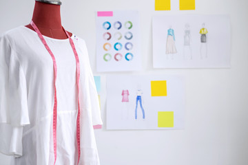 Red dummy in white clothes with measuring tape in tailors studio, Creative Design and Artistic Concept