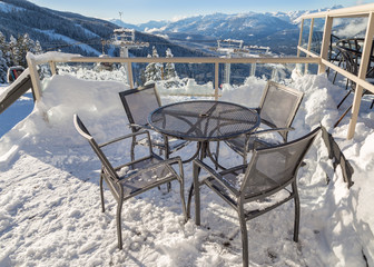 Chairs on a snow covered deck with a chairlift tower in the background.