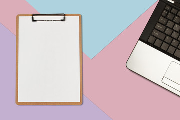 Clipboard with white sheet and laptop on pastel color background