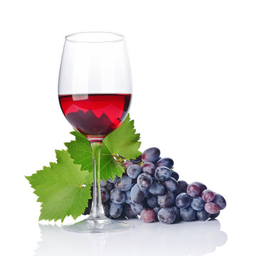 Glass with red wine for tasting with fresh grape and green leaf