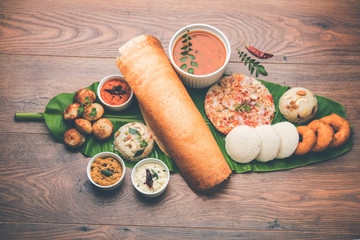 Group of South Indian food like Masala Dosa, Uttapam, Idli/idly, Wada/vada, sambar, appam, semolina halwa, upma served over banana leaf with colourful chutneys, selective focus