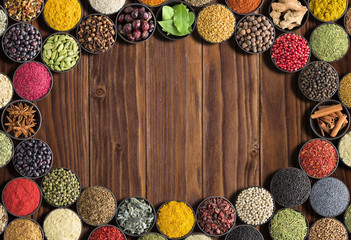 Fototapete - Indian Spices and herbs  with space for label. Various condiments on  wooden table, top view. Colorful seasoning for food
