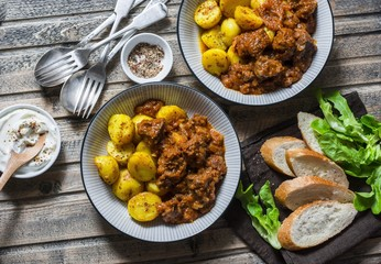 Served lunch table - irish beef stew with bombay turmeric potatoes. Delicious seasonal food on a wooden background, top view. Flat lay