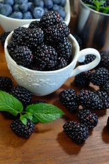 Close-up of  juicy blackberries in a bowl on rustic table