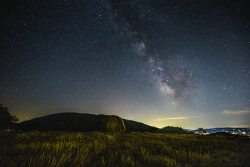 Beautiful view of starred night sky with milky way over a cultivated field with hay bale