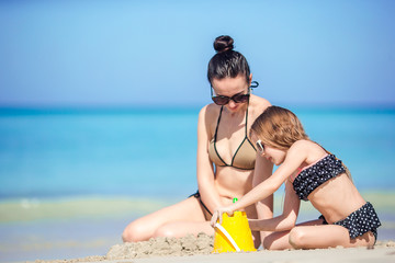 Mother and little kid enjoying beach summer tropical vacation.