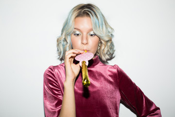 Portrait of beautiful girl in pink velvet blouse dreamily using noisemaker over white background isolated