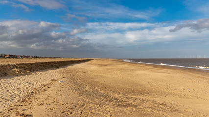 The beach in Great Yarmouth, Norfolk, England, UK - with some wind turbines of the Scroby Sands wind farm in the North Sea