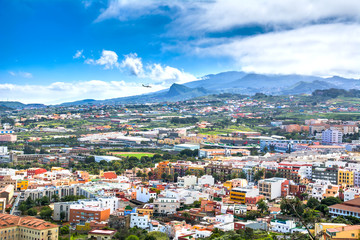 Aerial view of the residential area of Santa Cruz de Tenerife with airplane landing on Tenerife, Canary Islands. Spain