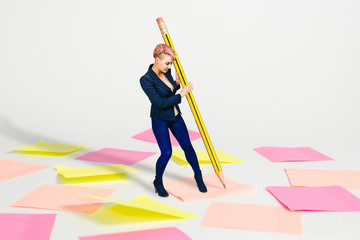 Young beautiful girl office worker writes in a huge pencil on a pink and yellow stickers background .