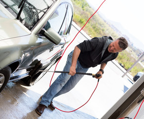 Car washing. Man cleaning car using high pressure water and brush outdoor