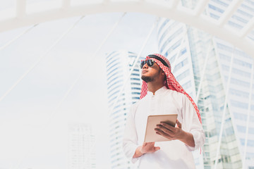 Handsome arab business man hold the digital tablet and looking to left side. Arab business man standing outside office. Finishing up a meeting, Connection concept. with copy space